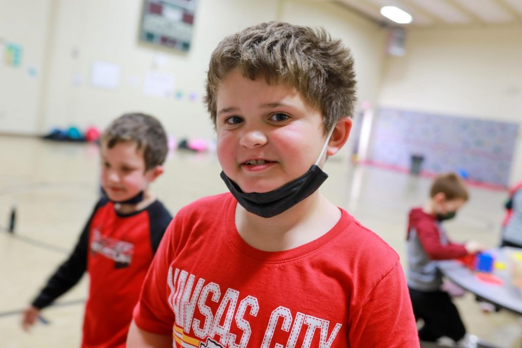 Elementary student smiling in a school gym