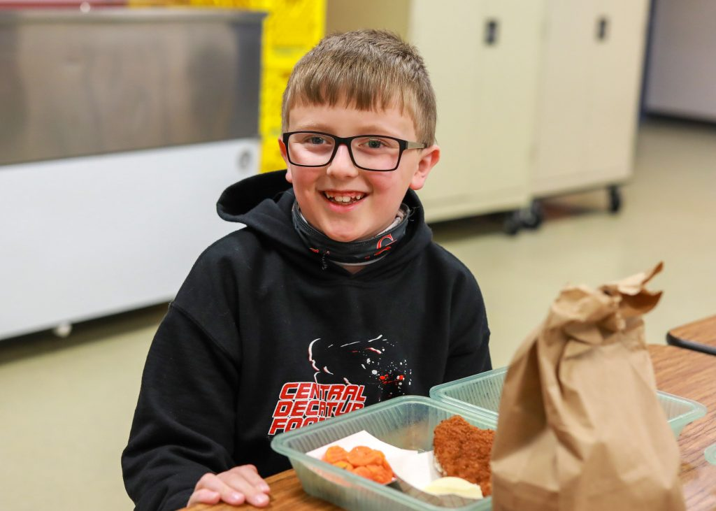 Elementary student with school lunch