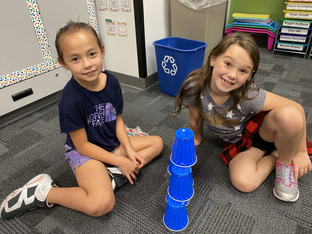 Third grade students work together to complete a teamwork activity.