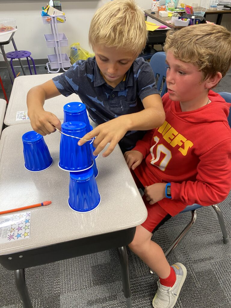 Two third grade students work together to stack blue cups.