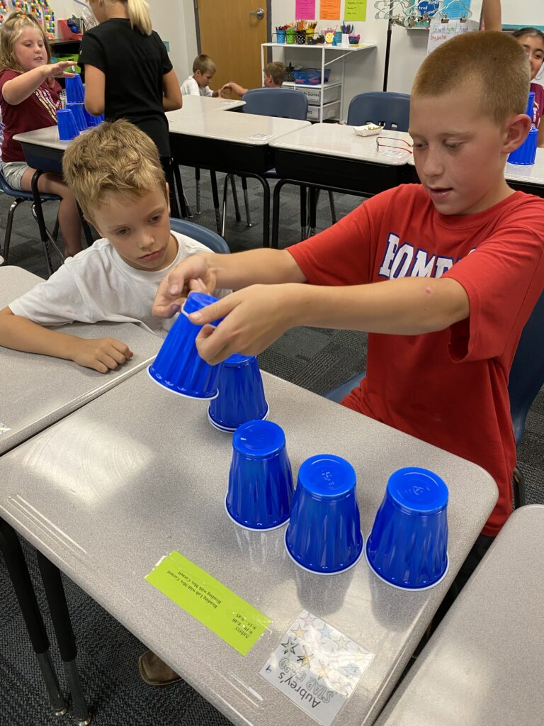 Third grade students work together to complete a science activity.