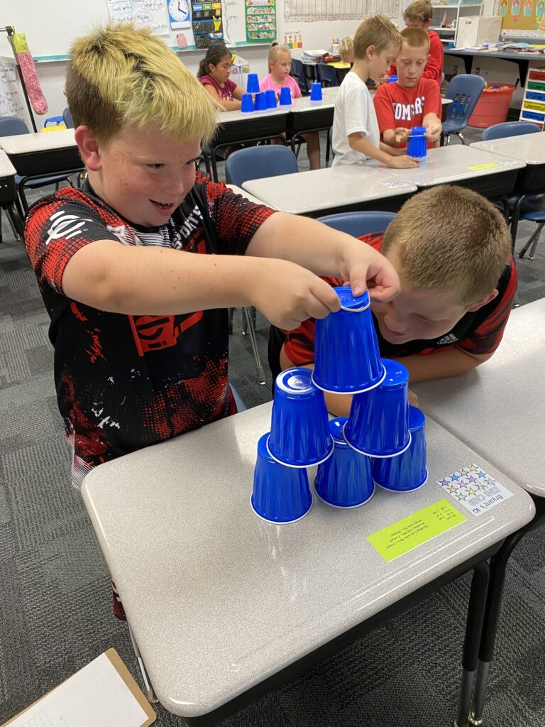 Two third grade students use teamwork to stack blue cups.