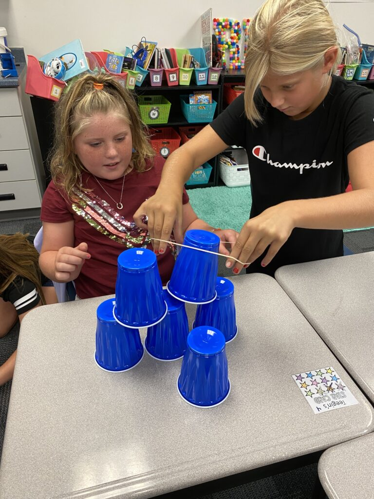 Two third grade students use teamwork to stack cups.
