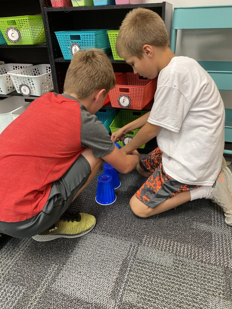 two third graders using teamwork to stack blue cups