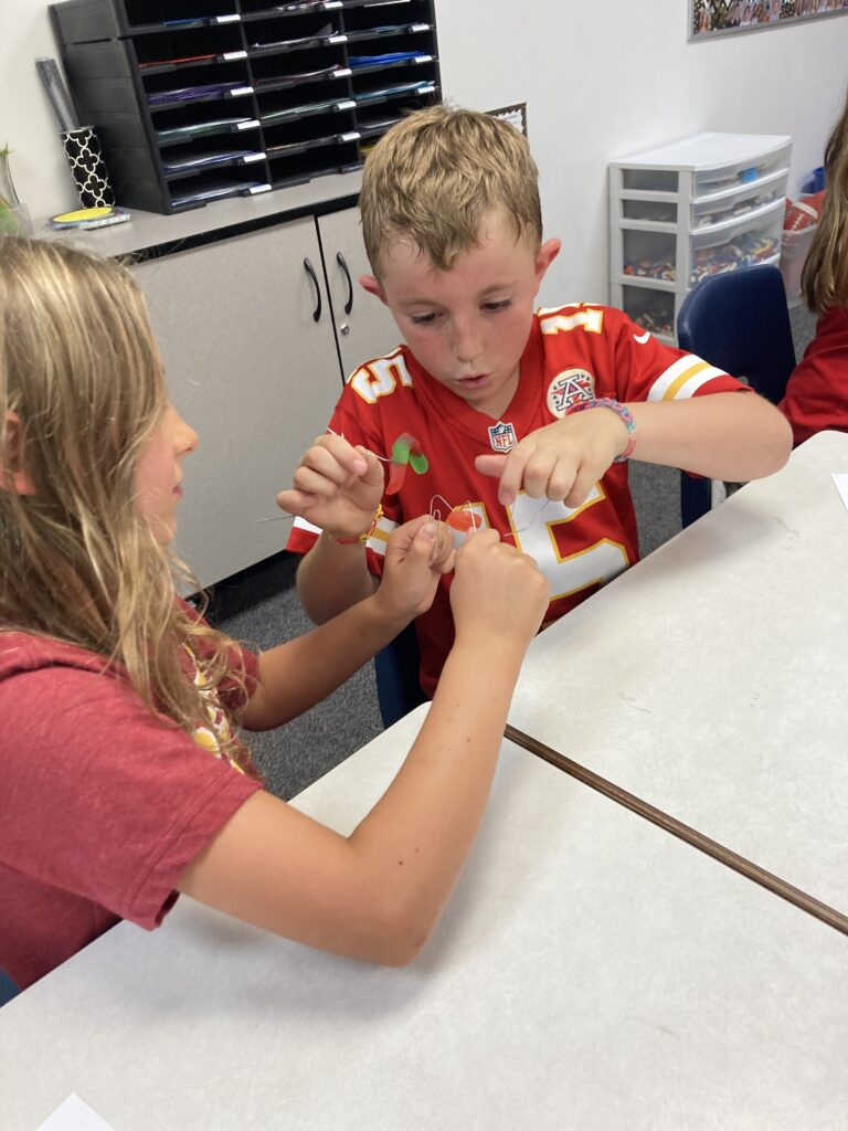 Third grade students work together to complete a science activity teamwork