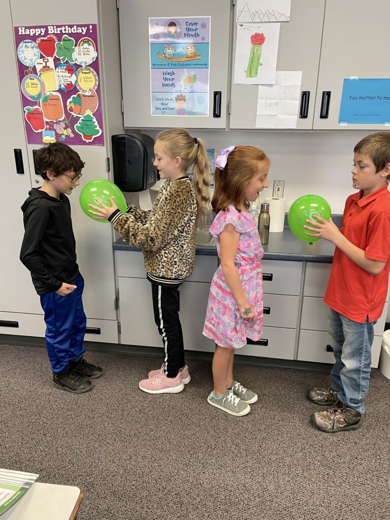 four fourth graders experiment with sound waves and ballonns