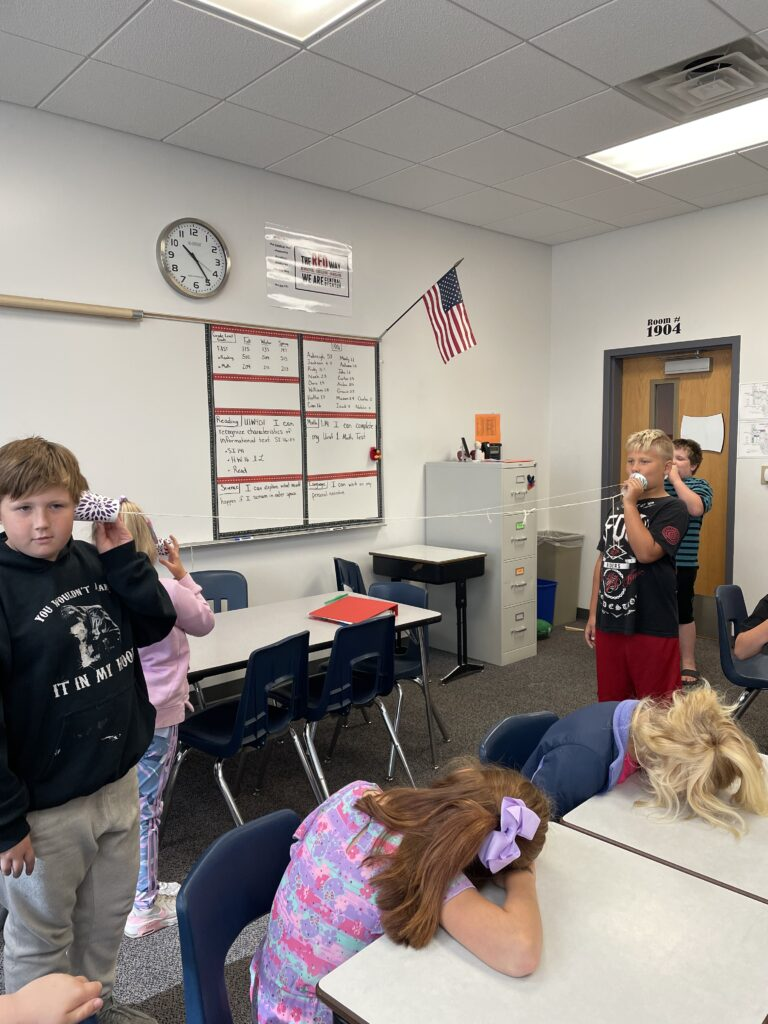 five fourth graders experiment with sound through tubes