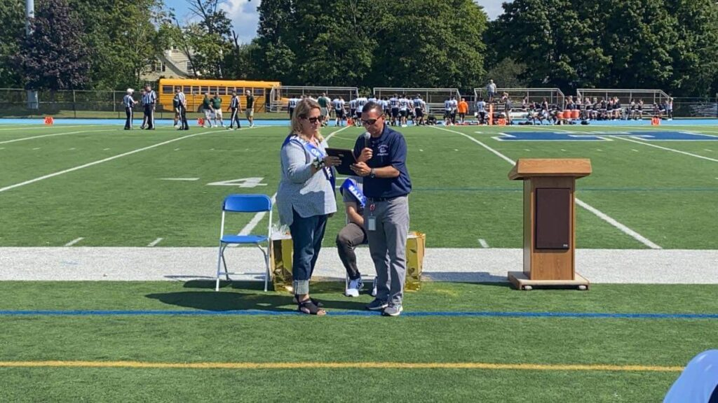 Kerry Welch receives her Hall of Fame plaque at a Hewlett High School football game.