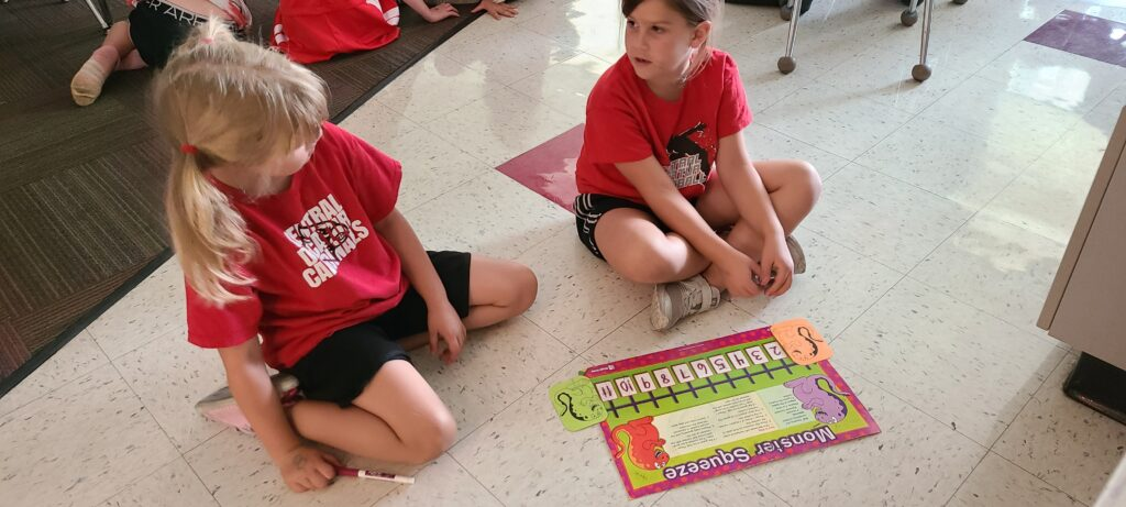 two first grade math students practice counting with a game
