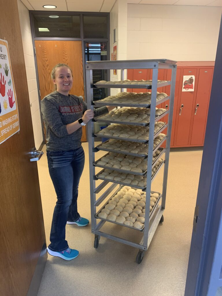 A culinary arts student shows the dinner rolls that will be baked for all music night.
