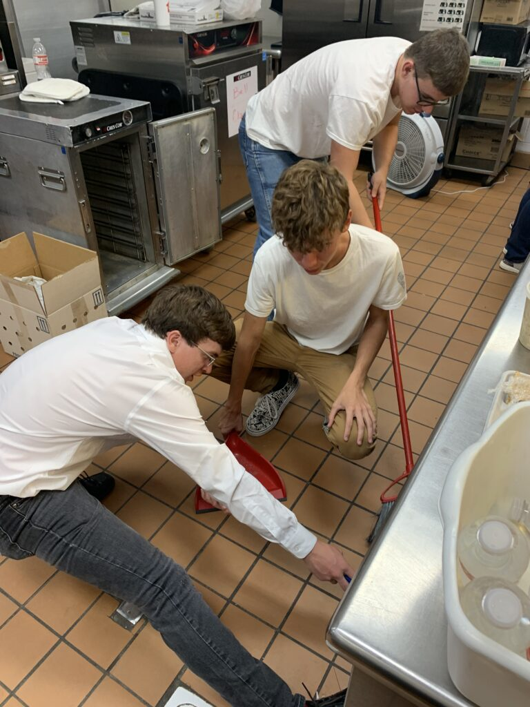 Three advanced culinary arts students clean up after the all music night meal prep