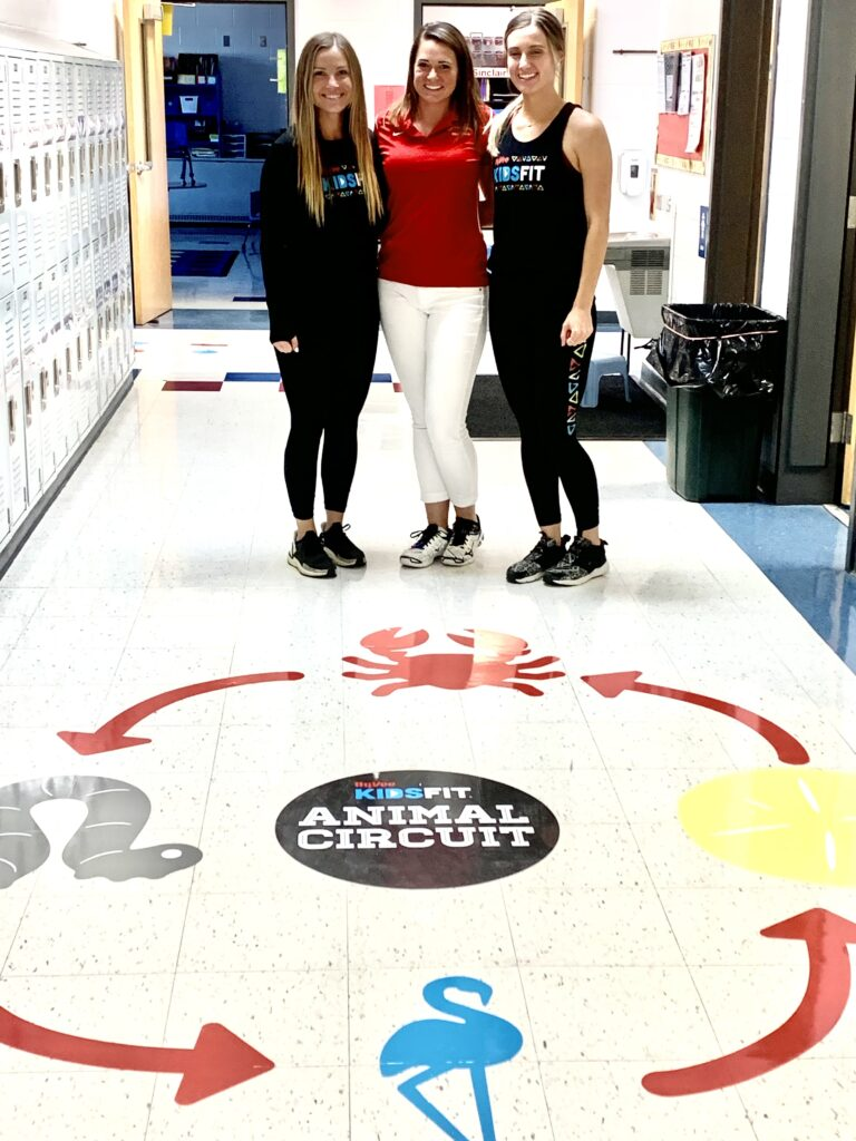 Mrs. Sinclair (center) stands with HyVee KidsFit team members