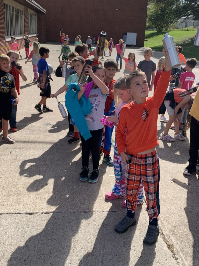 a large group of students hold their new water bottles high as they celebrate RED way behavior