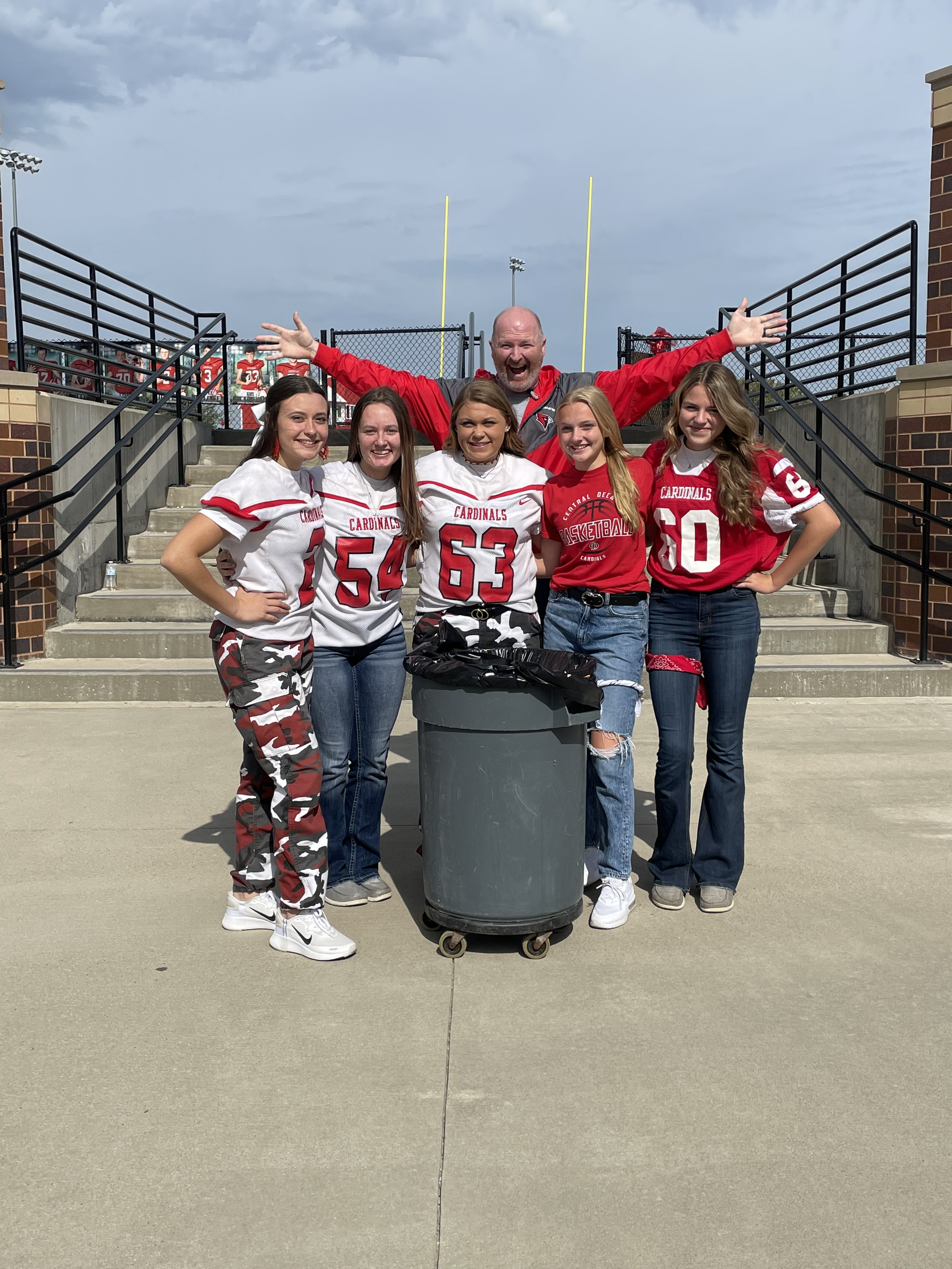 Five high school students gather around a trash can after being recognized for their RED way behavior