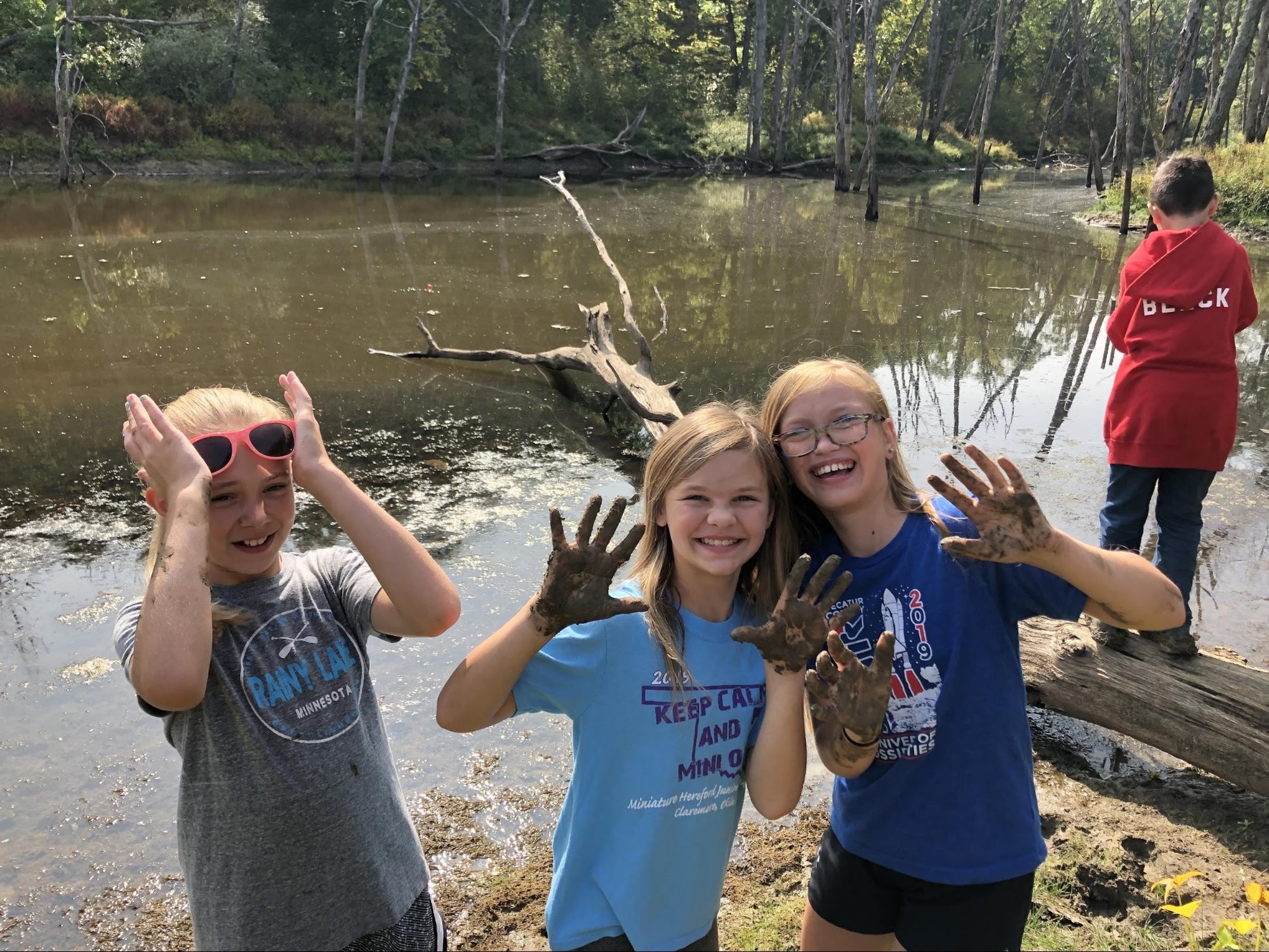 Elementary students standing in front of a lake, holding up muddy hands