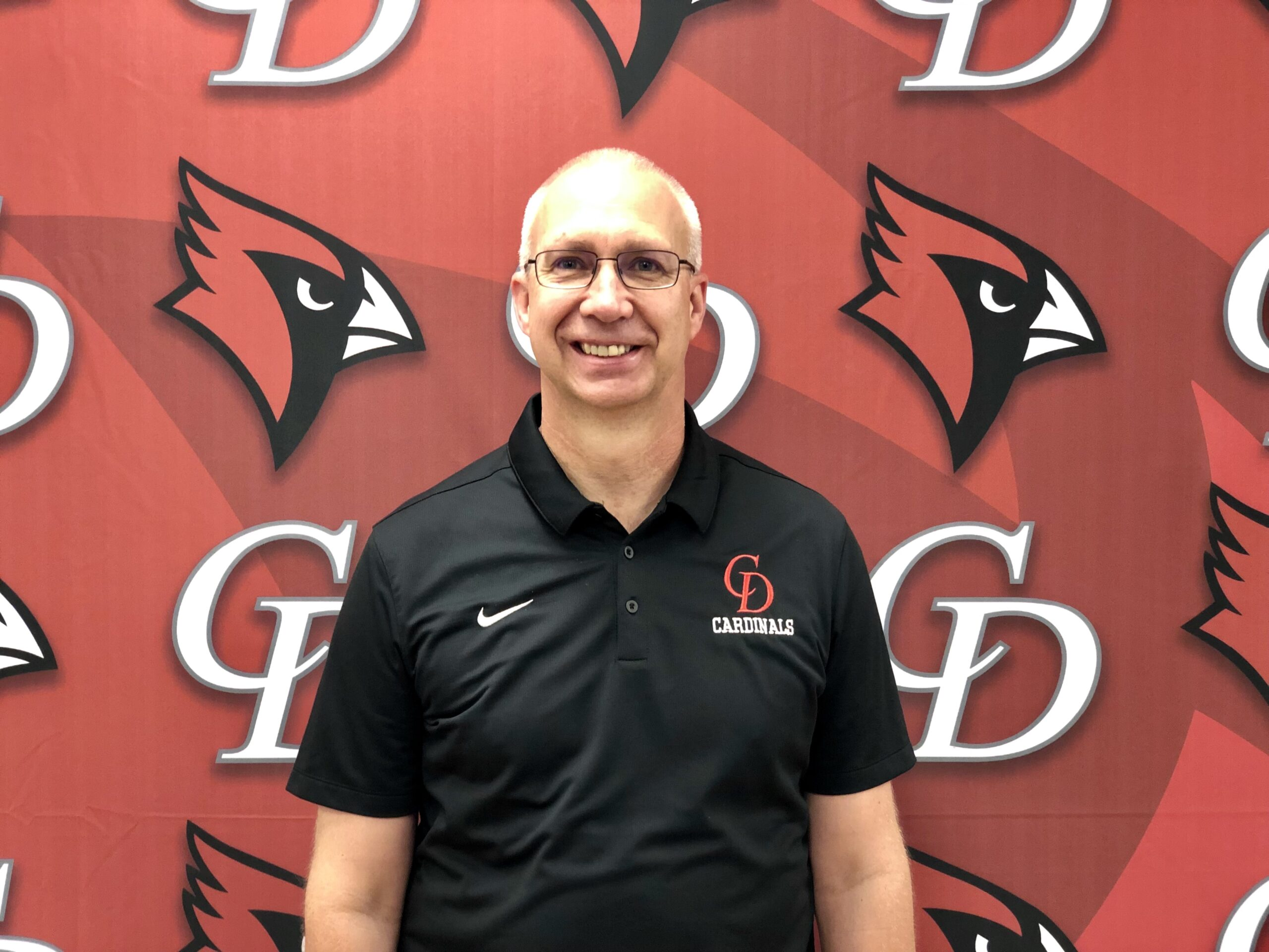 Dan Johnson, new Jr-Sr high principal stands in front of the red Central Decatur Cardinal logo.