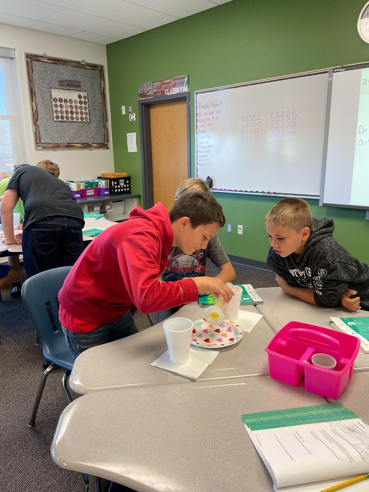 two 6th Grade student mix liquids during Ratio Work in math