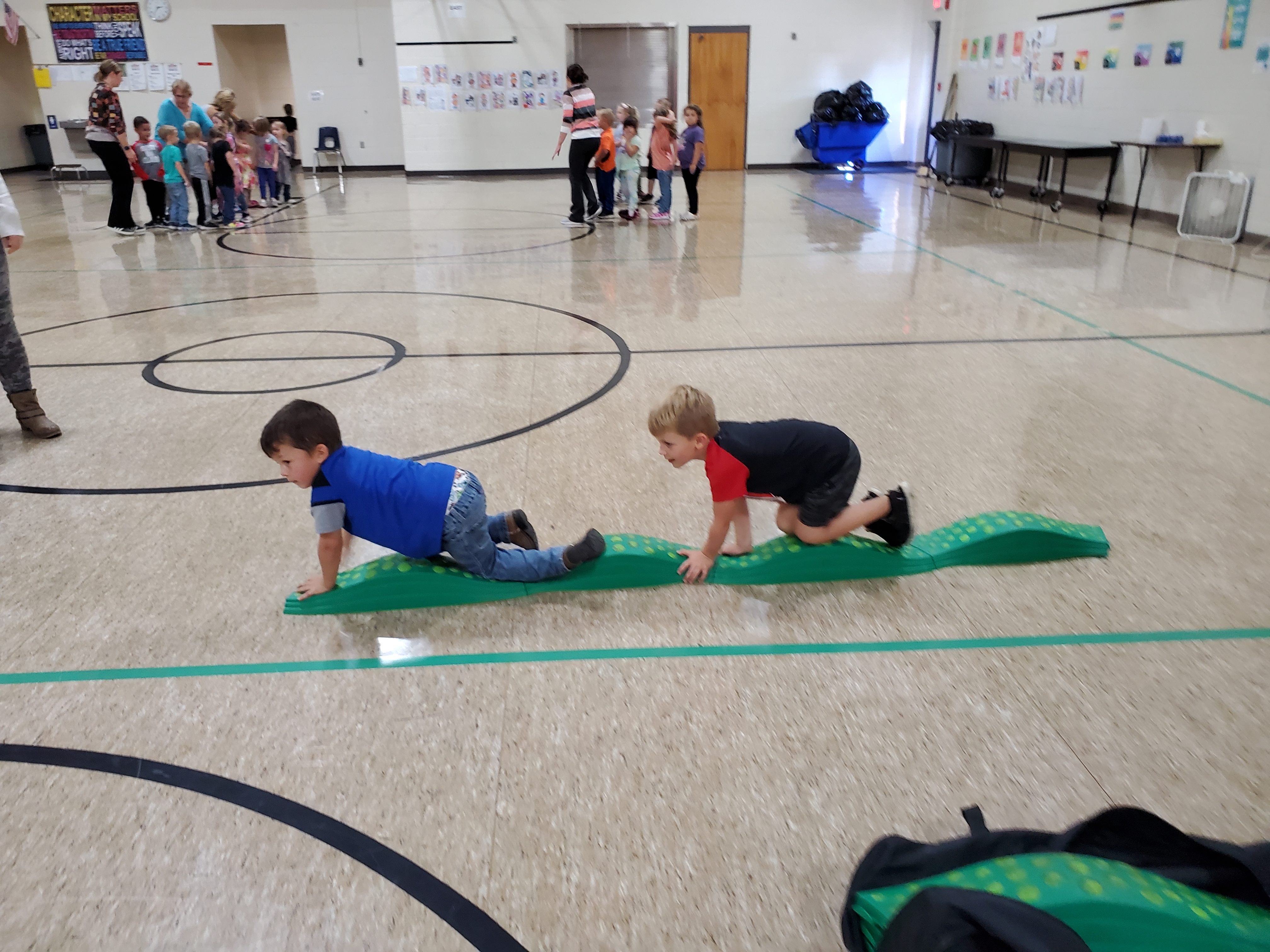 Two preschool students crawl in a line during PE class.